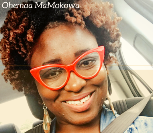 black woman smiling wearing red glasses